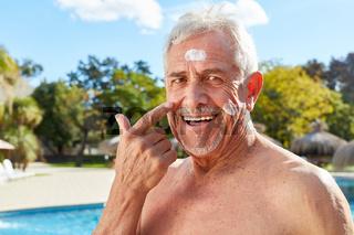 Senior cremt Gesicht mit Sonnencreme ein