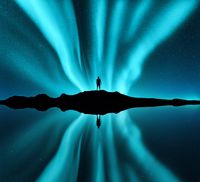 Aurora borealis and silhouette of standing man on the hill