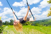 Happy female traveller swinging on wooden swing, enjoying summer vacation among pristine green rice terraces.