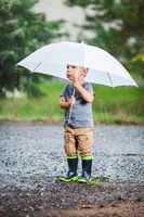 Adorable child holding an umbrella during a rain storm