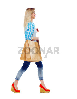 Side view of a woman walking with shopping bags.