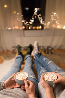 close up of couple drinking hot chocolate at home
