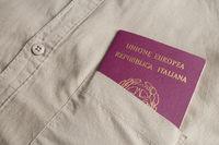 An italian passport out of a green shirt pocket