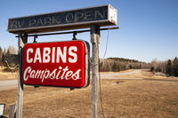 A Red Hanging Neon Roadside Sign Says Cabins and Campsites