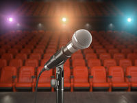 Microphone on the stage of concert hall or theater with red seats and spot light.