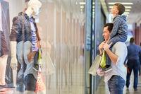 Vater mit Sohn auf den Schultern beim Einkaufen