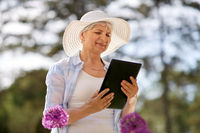 senior woman with tablet pc and flowers at garden
