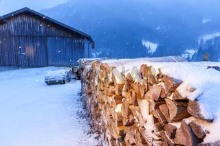 Firewood near a barn illuminated at evening