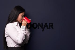 Businesswoman enjoying coffee break holding red cup