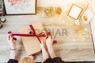 Woman wrapping present in paper with red ribbon.