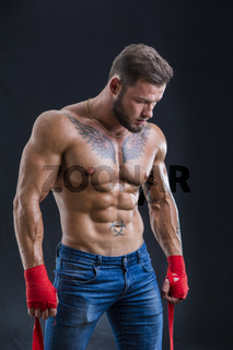 Muscular topless boxer man against black