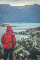 Man standing in a rain looking at Kotor town