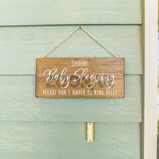Square frame Baby Sleeping sign hanging on the green wall and above the doorbell of a home