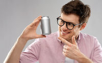 happy young man holding tin can with soda