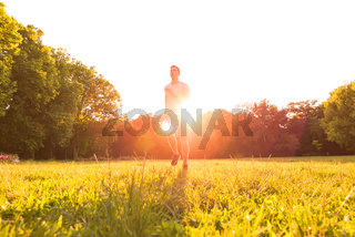 A handsome young man running during sunset in a park