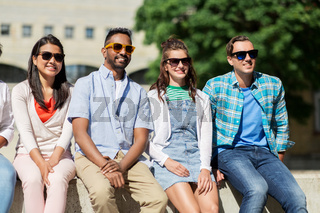 group of happy friends in sunglasses in city