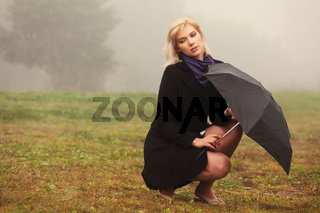 Young fashion woman with umbrella in a fog outdoor