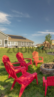 Vertical frame Backyard chairs around a stone fire pit adjacent to a picnic table with bench