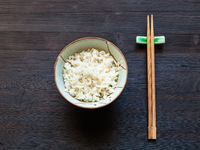 boiled rice in bowl and chopsticks on rest on dark