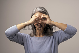 Asian mature woman does ok gesture like binoculars.