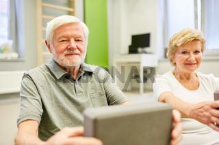 Senioren trainieren im Yoga Kurs mit dem Yogablock