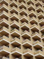 high rise building with residential flats or apartments in a yellow concrete and brick development with balconies