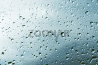 Blurred textured background of window panes with a cloudy background. Natural pattern from a drop of rain on a cloudy background