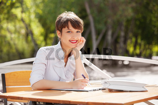 Young fashion business woman working at sidewalk cafe