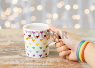 hand with cup of cacao and gay awareness wristband