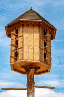 The wooden dovecote on the background of the blue sky at the summer countryside