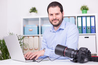 Bearded photographer at his office with laptop and camera.