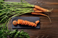 Top view at fresh organic Carrots on kitchen wooden table