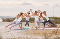 Group of women practising asana exercise Virabhadrasana Warrior I Pose