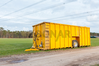 Large yellow manure tank standing in meadow