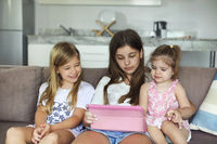 Three kid sisters girls playing together with tablet pc on white sofa