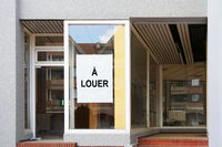 french vacancy sign in empty shop window reads a louer meaning for rent