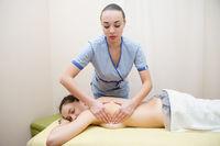 Masseuse makes massage to a cute brunette