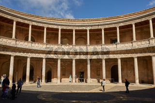 People visiting courtyard in Palacio de Carlos V in La Alhambra, Granada, Spain