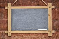 blank slate blackboard against rustic wood