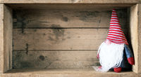 Christmas decoration with a gnome in a wooden box background