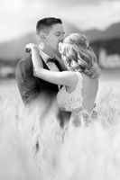 Groom hugging bride tenderly and kisses her on forehead in wheat field somewhere in Slovenian countryside.
