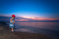 Girl walking on the seashore at dusk
