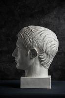 Gypsum copy of ancient statue Germanicus head on dark textured background. Plaster sculpture man face.