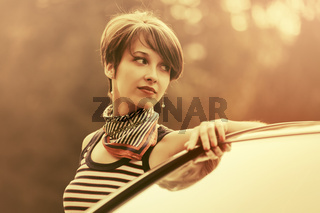 Happy young fashion woman with pixie hair leaning on her car