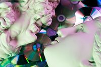 Antique statues of woman and man heads close up on a glitter CDs background. Concept of music, style, vintage, love.