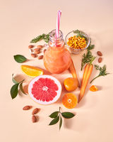 Fresh juicy detox smoothies in glass cup with orange berries, vegetables, fruits, almonds on a yellow paper background. Top view.