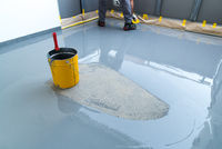 construction worker renovates balcony floor and spreads watertight resin and glue before chipping and sealing