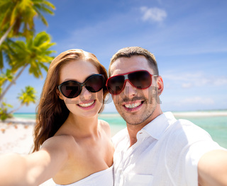 couple in sunglasses making selfie over beach