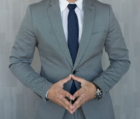 Torso of anonymous businessman standing with hands in lowered steeple wearing beautiful fashionable classic grey suit, white shirt and blue tie.