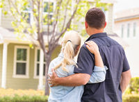 Happy Caucasian Couple Facing Front of House
